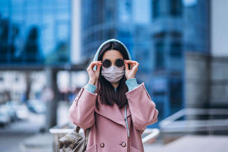 Female in medical mask outdoors in the empty city. Health protection and prevention of virus outbreak, coronavirus, COVID-19, epidemic, pandemic, infectious diseases, quarantine concept Archivio Fotografico