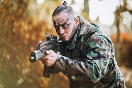 Portrait of a camouflage soldier with rifle and painted face playing airsoft outdoors in the forest. Side view. Stok Fotoğraf