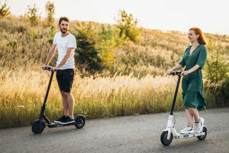 Portrait of young couple at sunset with beautiful natural landscape. Walking on electric scooters in the countryside.