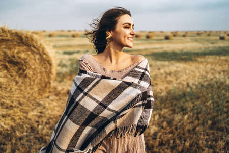 Closeup portrait of beautiful smiling woman with closed eyes. The brunette leaned on a bale of hay. A wheat field on the background.