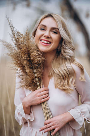 Photo of a pretty smiling girl with long blond curly hair in light long drees standing in a reed field and holding high reed branches in her hands
