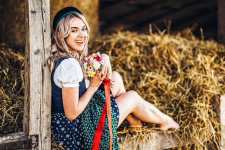 Cute blonde in dirndl, traditional festival dress with bouquet of field flowers sitting on the wooden fence at the farm with haystacks behind