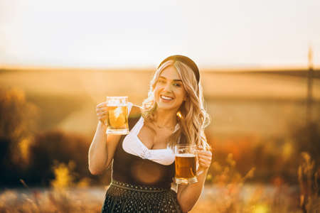 Pretty happy blonde in dirndl, traditional festival dress, holding two mugs of beer outdoors in the field with blurred background. Oktoberfest, St. Patrick's day, international beer day concept. Stock Photo