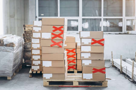 Stacks of cardboard boxes with products in the factory's packaging workshop. Some of them are marked with red tape.