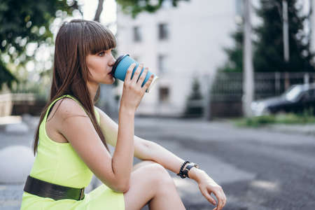 Pretty long hair brunette girl in green light dress with blue paper cup of beverage sitting outdoor on the street in the city Stockfoto