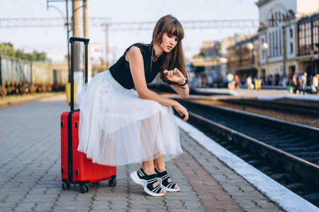 Female brunette traveler with red suitcase in white skirt waiting for a train on raiway station and checking time on her wristwatch