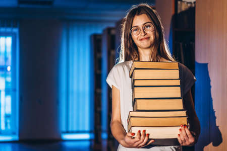 Young girl student with glasses in library smiling and carries stack of books. Exam preparation.