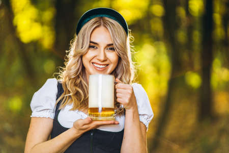 Pretty happy blonde in dirndl, traditional festival dress, holding mug of beer outdoors in the forest with blurred background. Oktoberfest, St. Patrick's day, international beer day concept.