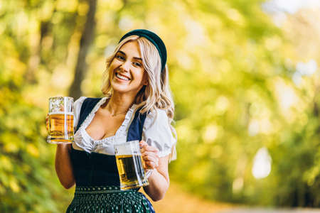 Pretty happy blonde in dirndl, traditional festival dress, holding two mugs of beer outdoors in the forest with blurred background. Oktoberfest, St. Patrick's day, international beer day concept. Stockfoto