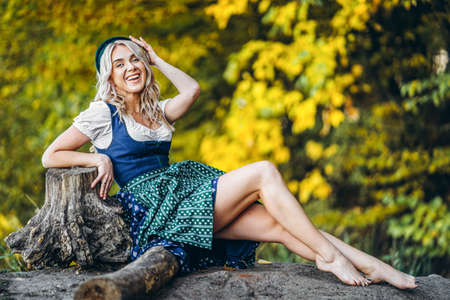 Oktoberfest, St. Patrick day, intenational beer day. Barefoot happy pretty blond girl in dirndl, traditional beer festival dress, sitting outdoors with blured colorful trees behind