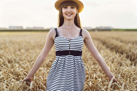 Pretty brunette girl in light dress wearing hat and walking outdoor in wheat field at sunset time