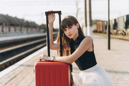 Female brunette traveler with red suitcase in white skirt waiting for a train on raiway station