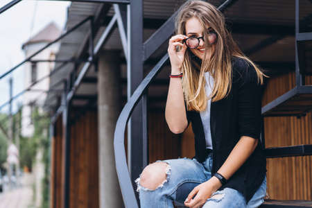 Beautiful girl with long hair and glasses sitting on metal stairs on the wooden background of house with vertical boards. Woman smiling and looking at camera. Archivio Fotografico
