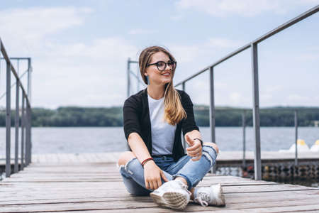Young woman with long hair in stylish glasses posing on a wooden pier near the lake. Girl dressed in jeans and t-shirt smiling and looking away Archivio Fotografico - 152873903