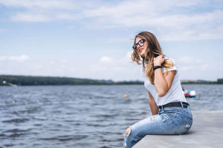 Young woman with long hair in stylish glasses posing on the concrete shore near the lake. Girl dressed in jeans and t-shirt smiling and looking away.