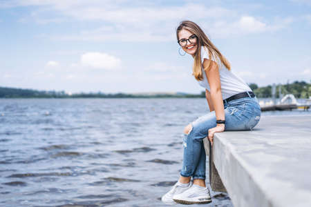 Young woman with long hair in stylish glasses posing on the concrete shore near the lake. Girl dressed in jeans and t-shirt smiling and looking at the camera. Archivio Fotografico - 152873973