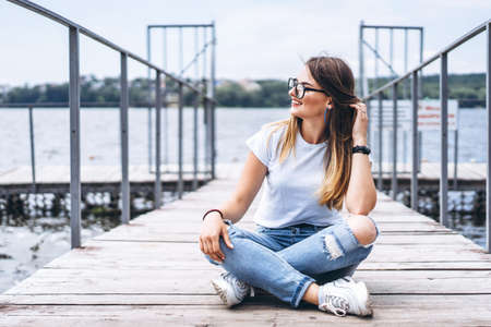Young woman with long hair in stylish glasses posing on a wooden pier near the lake. Girl dressed in jeans and t-shirt smiling and looking away