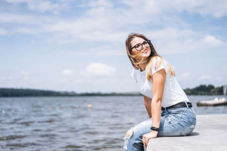 Young woman with long hair in stylish glasses posing on the concrete shore near the lake. Girl dressed in jeans and t-shirt smiling and looking away. Archivio Fotografico