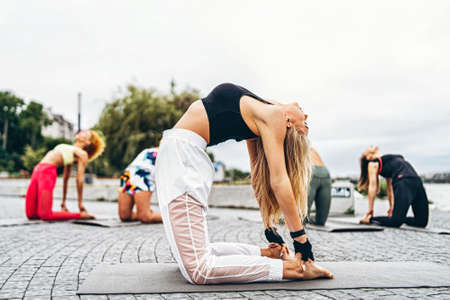 A group of sporty women are practicing yoga exercises on the mat on the street in the park with personal coach. Active lifestyle.