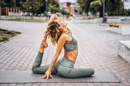 Sporty young woman with long hair in gray tracksuit doing stretching exercises on the street. Active lifestyle, yoga concept.