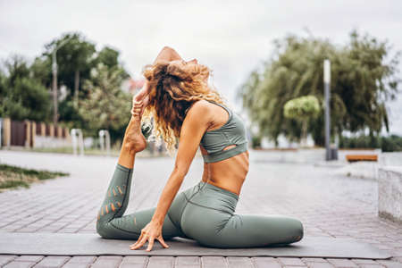 Sporty young woman with long hair in gray tracksuit doing stretching exercises on the street. Active lifestyle, yoga concept. Archivio Fotografico - 152873990