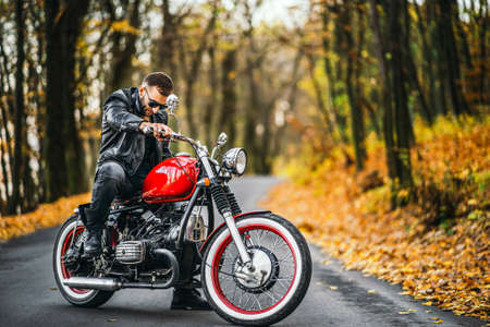 Bearded brutal man in sunglasses and leather jacket sitting on a motorcycle on the road in the forest with blured colorful background. Stock Photo