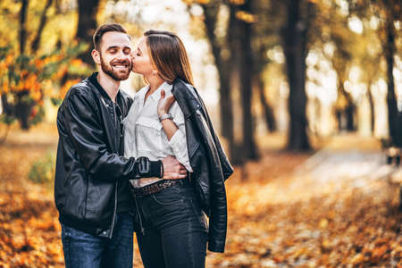 Portrait of a young loving couple. Man and woman hugging and smiling in the background of autumn park. 스톡 콘텐츠