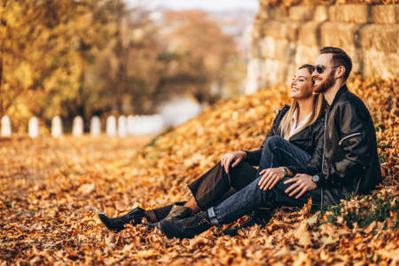 Portrait of a young loving couple, sitting in autumn leaf and enjoying nature. Love story. 스톡 콘텐츠