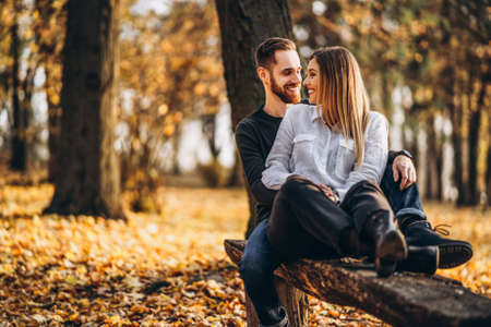 A young loving couple sitting on a wooden bench in the forest. Man and woman hugging and smiling on the background of autumn trees. 스톡 콘텐츠