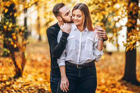 A young couple in love walking in the autumn park on a sunny day. The man gently hugs the woman. Love story. 스톡 콘텐츠