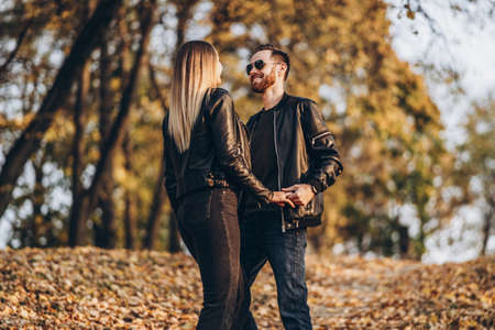 Beautiful young couple walking in the autumn park on a sunny day. They hug and smile, enjoy a walk. 스톡 콘텐츠