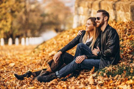 Portrait of a young loving couple, sitting in autumn leaf and enjoying nature. Love story. Archivio Fotografico