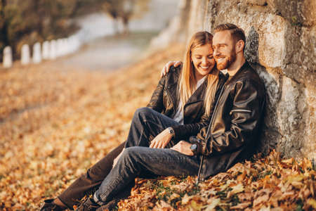Portrait of a young loving couple, sitting in autumn leaf near stone wall and enjoying nature. Love story.