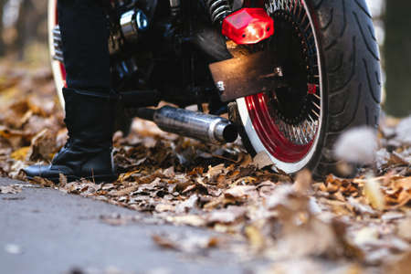 Close up photo of motorcycle exhaust while strarting up engine with rider on it outdoors on the road