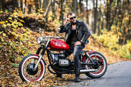 Bearded brutal man in sunglasses and leather jacket sitting on a motorcycle on the road in the forest with blured colorful background.