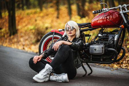 Pretty blonde biker girl in sunglasses sitting near red motorcycle on the road in the forest with colorful blurred background. Archivio Fotografico