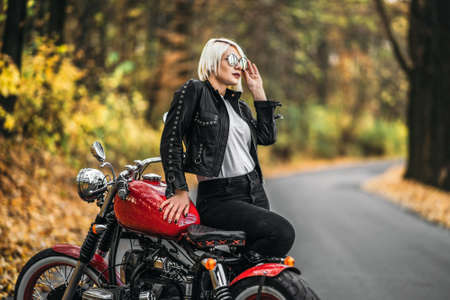 Pretty blonde biker girl in sunglasses with red motorcycle on the road in the forest with colorful blurred background.