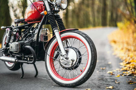 Red custom old fashioned motorcycle on the road in the forest with colorful blurred background