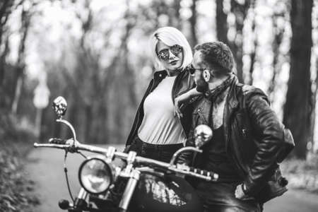 Black and white photo of pretty couple near motorcycle on the road in the forest with blured background. Relationship concept.