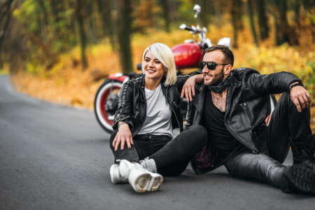 Pretty couple sitting near red motorcycle on the road in the forest with colorful blured background. Relationships concept.