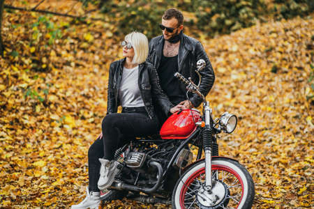 Pretty couple near red motorcycle on the road in the forest with colorful blured background. Relationship concept.