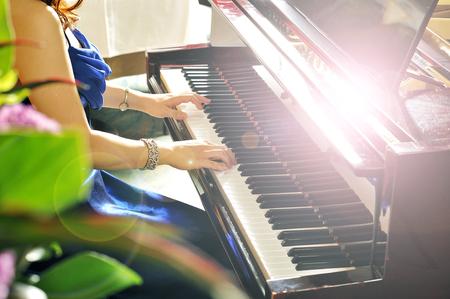 piano: Mujeres que juegan el piano de cola en la sala de