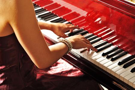 部屋でグランド ピアノを弾く女性