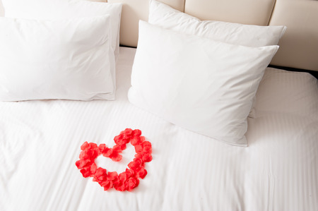 pillows: Heart of red petals on bed Stock Photo