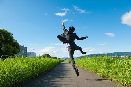 saltando: Desde detrás del hombre de negocios de saltar