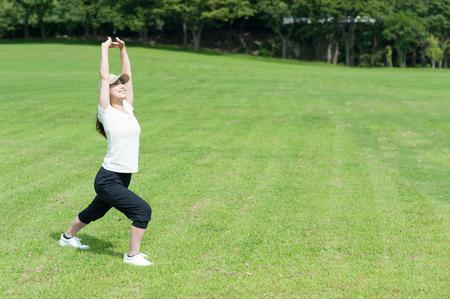 ejercicio aeróbico: Mujer que estira en un parque