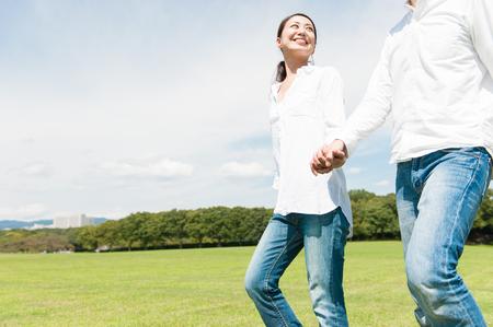 美しい女性が公園で彼女のボーイ フレンドの手をリード