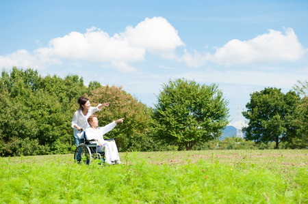 family life: Senior riding in a wheelchair in the park