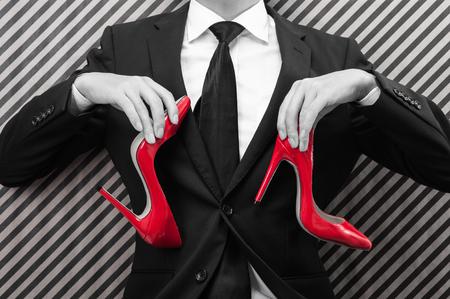 赤いハイヒールを持っているビジネスマン