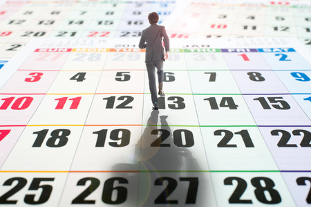 hard day at the office: Businessman walking on the calendar